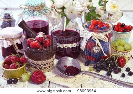 Fresh berry in assortment, spoon and vintage glass jars on the napkin. Making fruit jam concept. Fresh berry on wooden table, summer still life and rustic food vintage background. Preserved fruits