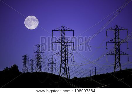 high tension power lines and towers silhouetted at night with full moon in background