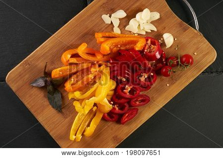 Fresh vegetables on cutting board fresh juicy tomato garlic basil and bell pepper. Healthy Ingredients for vegetarian dish. Top view
