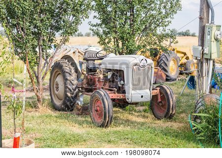 Old gray tractor sitting on a farm.