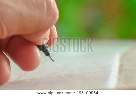 Close up human hand use pen whiting something on paper with nature blurred background