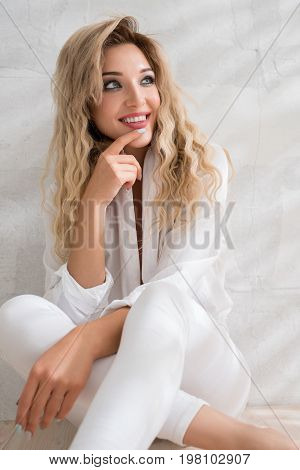 Seductive curly blonde wearing sexy white shirt and jeans sitting on the floor near the brick wall in studio