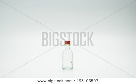 Small glass bottle with narrow neck design and red cap