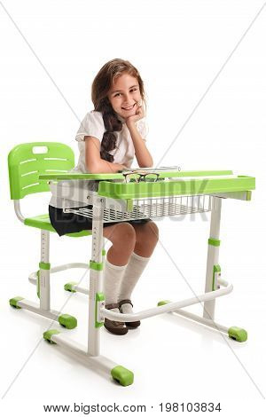 Young cheerful smiling schoolgirl sitting at the desk on lesson