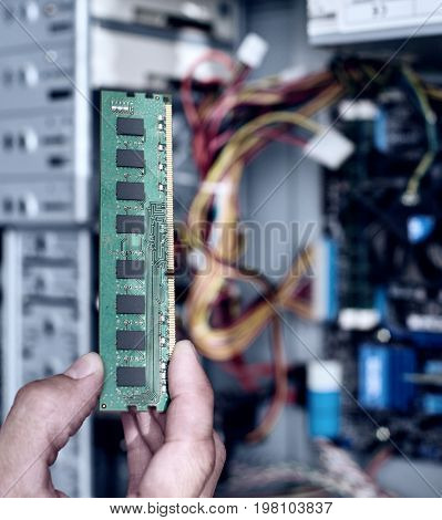 Computer engineer installing RAM Memory card, close up photo. Square aspect ratio with toning