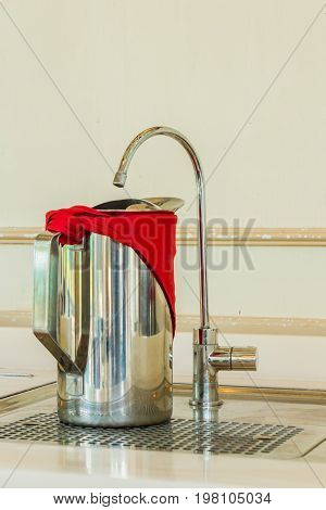 Stainless steel jug of cold water and Faucet filter on table in domestic Kitchen.