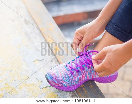 Running shoes - closeup of woman tying shoe laces. Female sport fitness runner getting ready for jogging.