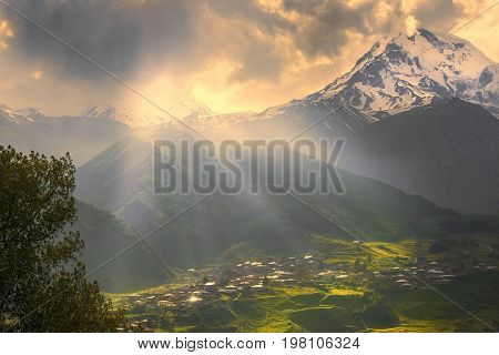 sunrise over the Caucasus Mountains. Gergeti village in the foreground and Mount Kazbek in the background, Kazbegi region, Georgia