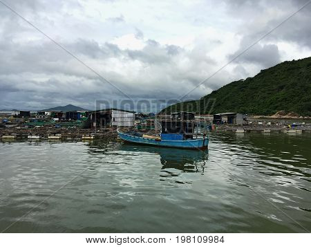 the fishing floating village on the water in Vietnam, shabby huts, the pantones, the boat in the foreground, near the mountains
