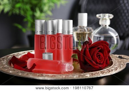 Perfume bottles and rose on tray
