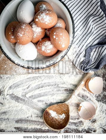 Empty eggshells on table sprinkled with flour, topview