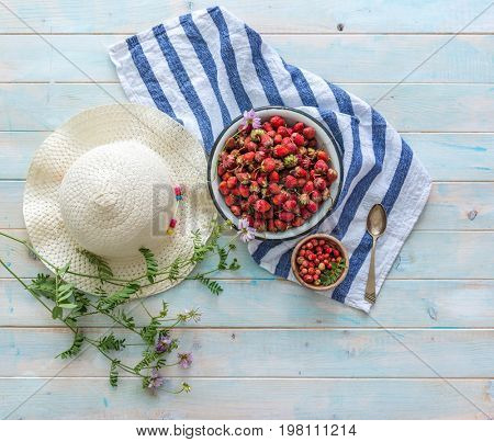 Bowl of strawberries, striped napkin, straw hat, topview