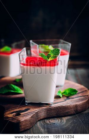 Delicious Italian dessert Panna Cotta with raspberry sauce coulis served for three in small transparent glasses.