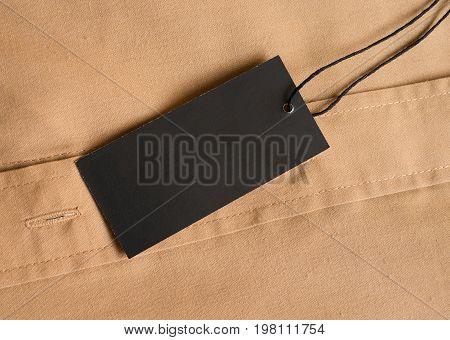 Black label price tag on beige shirt. Mockup for price or brand presentation.
