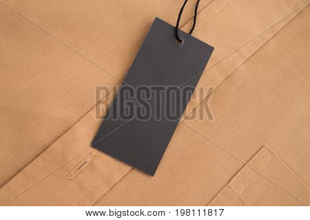 Label price tag on beige shirt. Mockup for price or brand presentation.