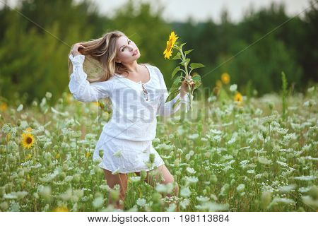 Woman in a field with a sunflower in her hand she strokes her long hair.