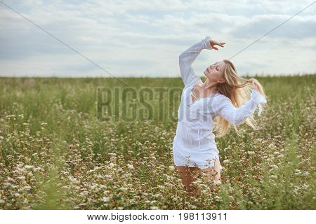 Woman stands in the field and enjoys nature.