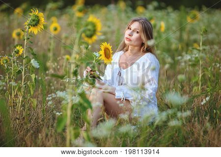 Young woman sitting in a field among sunflowers on a bright summer day.