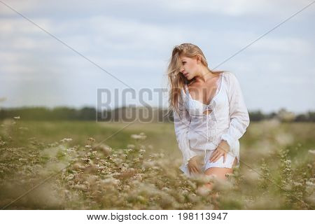 Beautiful woman in a field among the tall grass is nurtured by nature.