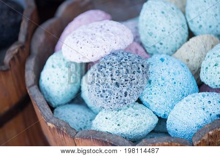 pumice stones colored blue and white abrasive porous minerals for foot care and spa salon in wooden bucket at market