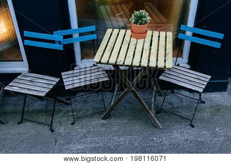 three wooden chairs and a table on the street next to a cafe window with flowers