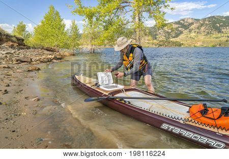 Fort Collins, CO, USA - August 2, 2017: A senior paddler is launching Starboard Expedition paddleboard with a home made hatch on a shore of Horsetooth Reservoir.