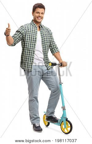 Full length portrait of a young guy with a scooter making a thumb up gesture isolated on white background