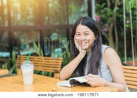 Asian Women Holiday Education Self-learning With Book In Garden With Coffee Shop.