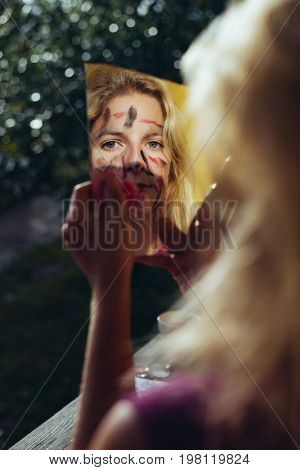 Face painted woman looking at broken mirror.