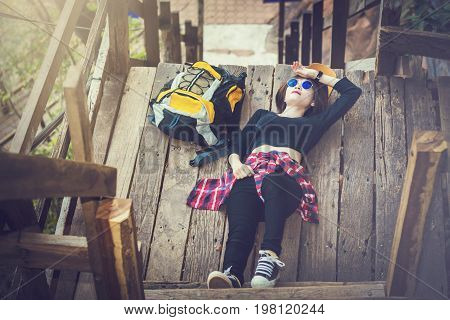 A Young Girl Napping On A Wooden Bridge In The Mountains.