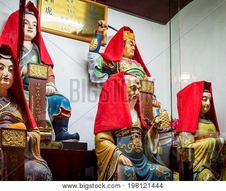 Shanghai, China - Nov 6, 2016: Inside the 600-year-old Old City God Temple. A few rare figurines of Taoist deities displayed in glass cabinet. Some reflections can be seen. Low-light image.