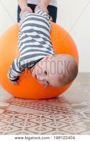 Sad little boy lying upside down on a fitball being supported with a parent.