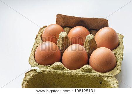 chicken eggs in carton on white background