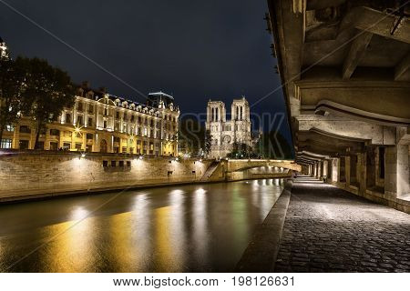 Notre Dame Cathedral view from the Seine river bank at dusk in Paris, France