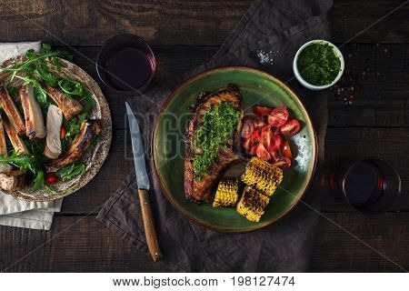 Grilled steak with chimichurri sauce and red wine over wooden table. Top view. Dinner table