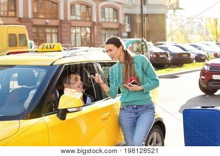 Young woman talking to male taxi driver while standing near car