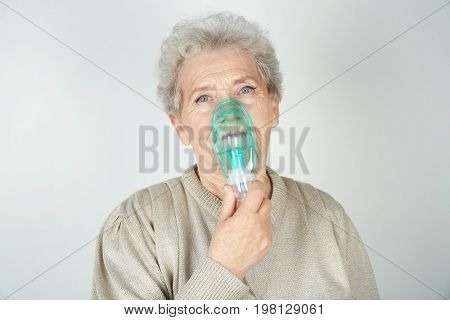 Elderly woman using asthma machine on light background