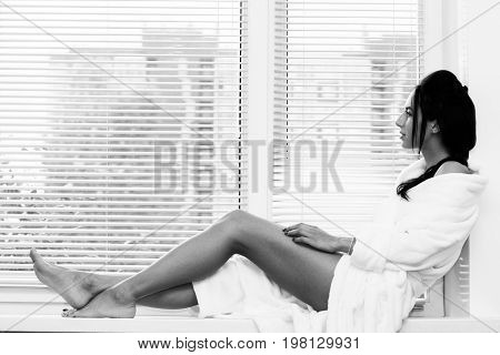 beautiful woman in white dressing gown sitting on windows with blinds, monochrome