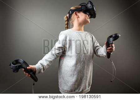 Cute Little Child Girl Playing Game In Virtual Reality Glasses And Two Joysticks