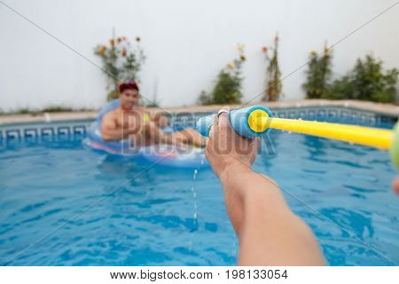Young friends shooting with water guns at each other while having fun in pool.