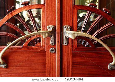 Old stylish wooden door with nice brass doorknob