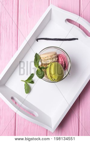 Colored macaroons, mint and vanilla bean on a pink background