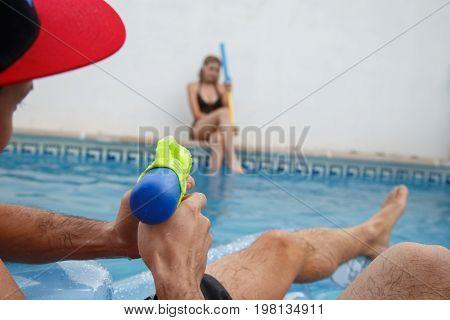 Young friends having fun with water guns.