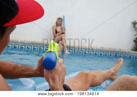 Back view of man on inflatable mat shooting at girl with water gun while relaxing in pool.