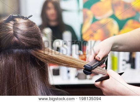 hairdresser straightening long brown hair with hair irons