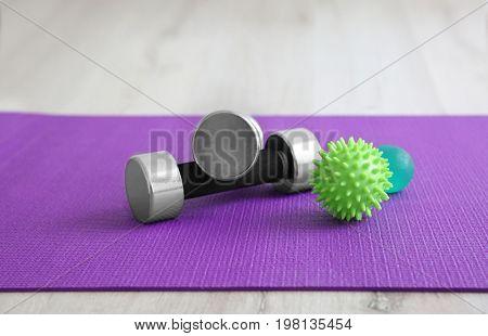Massage balls and dumbbells on mat
