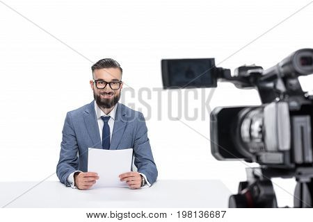 Smiling Male Newscaster With Papers Sitting In Front Of Camera, Isolated On White