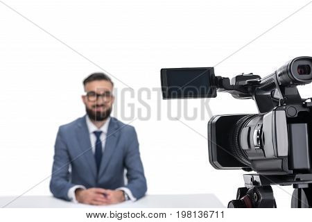Selective Focus Of Male Newscaster Sitting In Front Of Camera, Isolated On White