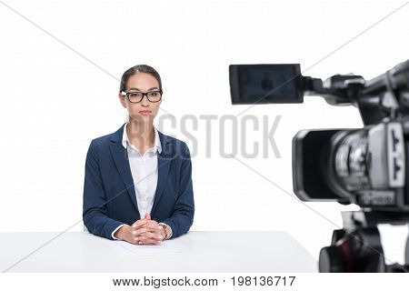 Female Newscaster In Suit Sitting In Front Of Camera, Isolated On White