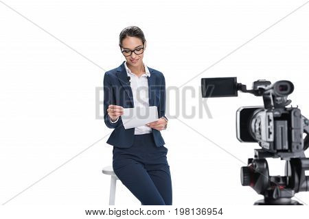 Beautiful Smiling Female Newscaster With Papers Sitting In Front Of Camera, Isolated On White